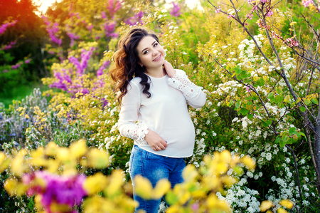 84961105 - pregnant woman standing in flowers